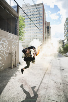Cool young man doing parkour backflipping with powder cannon in urban alley - HEROF17589