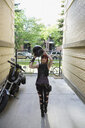 Cool woman with ripped jeans removing motorcycle helmet in urban alley - HEROF17595