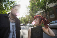 Cool couple blowing bubble gum on urban street - HEROF17604