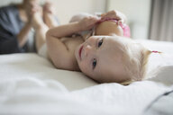Close up portrait smiling baby girl laying on bed with doll - HEROF17616