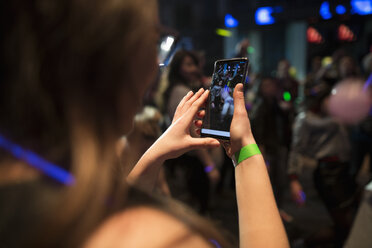 Young female millennial using camera phone at night club party - HEROF17712