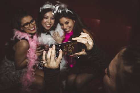 Young female millennial with camera phone photographing friends at bachelorette party - HEROF17727