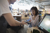 Worker helping active senior woman paying with smart phone contactless payment at grocery store checkout - HEROF17760