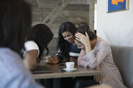 Women friends drinking coffee and using smart phone in cafe - HEROF17763