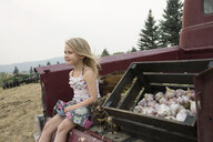 Carefree blonde girl sitting next to crate of harvested garlic in truck bed - HEROF17877