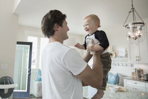 Father holding happy baby son in kitchen - HEROF18048
