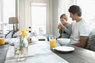 Father holding son drinking orange juice at breakfast nook - HEROF18051