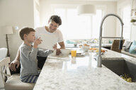 Father and son eating breakfast and using digital tablet at kitchen island - HEROF18057