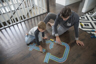 Father and son playing with track toy on floor - HEROF18063