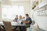 Family using digital tablet in breakfast nook - HEROF18069