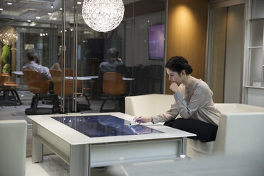 Focused businesswoman using interactive touch table in office - HEROF18078