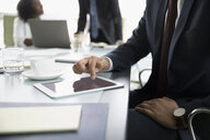 Close up businessman using digital tablet in conference room meeting - HEROF18129