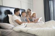 Family relaxing, using digital tablet in bed - HEROF18177