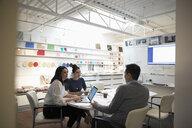 Designers brainstorming, using laptop in creative office - HEROF18240