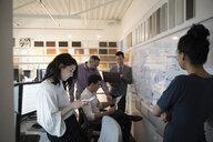 Designers brainstorming, meeting at whiteboard in creative office - HEROF18252
