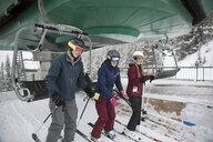 Family skiers getting off chair lift at ski resort - HEROF18297
