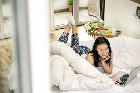 Young woman lying bed, using laptop in the morning - PESF01202