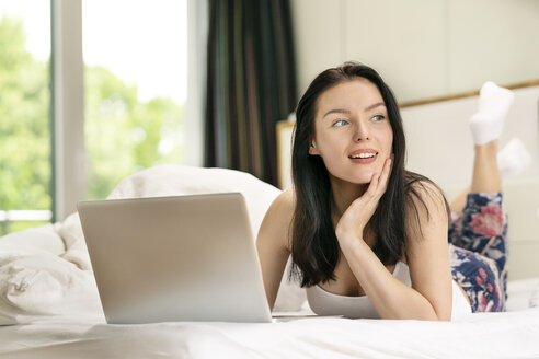 Young woman lying bed, using laptop in the morning - PESF01205