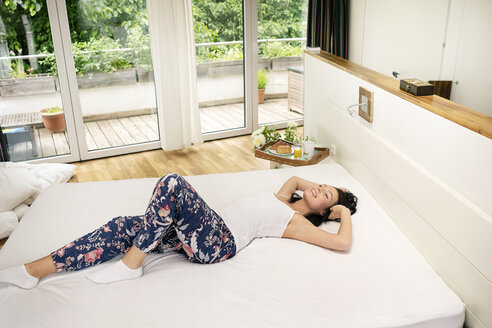 Young woman lying on bed, satretching in the morning - PESF01208