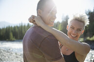 Affectionate smiling couple hugging in sunny summer woods - HEROF18379