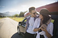 Affectionate young couple hugging outside car on sunny rural roadside, enjoying summer road trip - HEROF18394