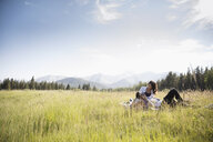 Affectionate young couple relaxing in sunny summer rural field below mountains - HEROF18400