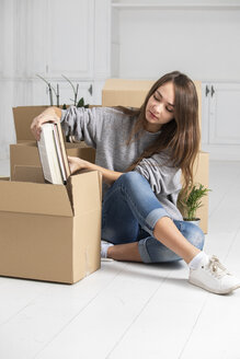 Woman sitting on the floor packing cardboard boxes - ERRF00732