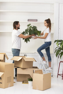 Couple unpacking cardboard boxes and furnishing new home - ERRF00741
