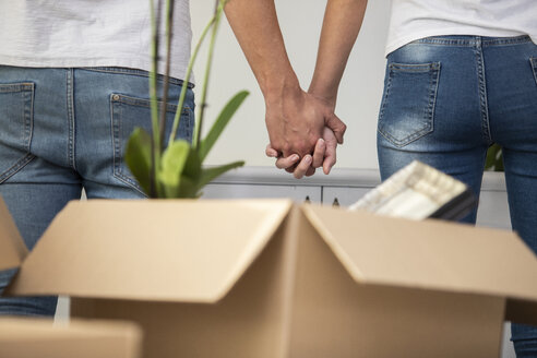 Close-up of couple with cardboard boxes standing hand in hand in new home - ERRF00747