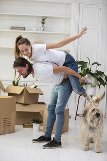 Happy couple with dog and cardboard boxes in new home - ERRF00753