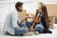 Man handing over tiny house model to girlfriend surrounded by cardboard boxes - ERRF00765