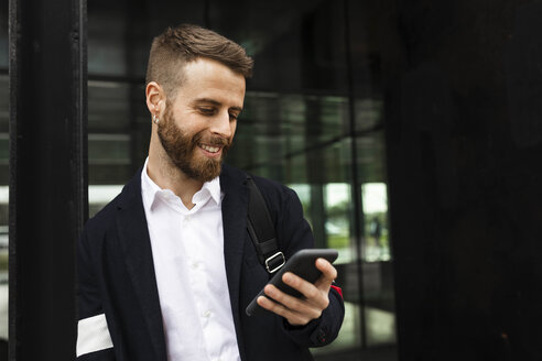 Smiling stylish businessman using cell phone in the city - JRFF02580