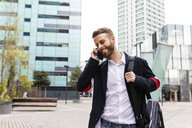 Stylish businessman talking on cell phone in the city - JRFF02583