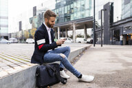 Stylish businessman sitting in the city using cell phone - JRFF02586