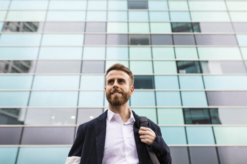 Stylish businessman in front of office building looking around - JRFF02589