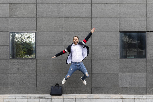 Excited businessman jumping in front of building - JRFF02595