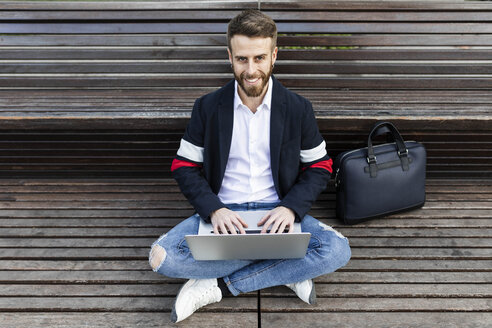 Spain, Barcelona. Young business man outside the office sitting on the floor using the laptop. - JRFF02598
