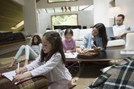 Family in pajamas coloring and reading in living room - HEROF18427