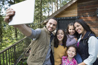 Family taking selfie with digital tablet camera on cabin balcony - HEROF18430
