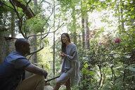 Couple talking outside cabin in woods - HEROF18439