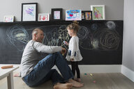Father and daughter drawing on blackboard wall - HEROF18502