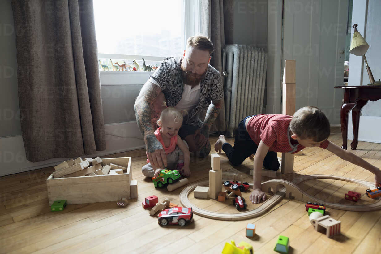 Father and children playing with wood blocks and toy train on floor - HEROF18544 - Hero Images/Westend61