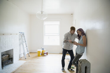 Couple using cell phone in empty new house - HEROF18553