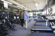 Couple browsing cardio machines in home gym equipment store - HEROF18592
