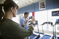 Couple with camera phone photographing treadmill in home gym equipment store - HEROF18595