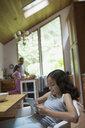 Girl using digital tablet at kitchen table - HEROF18604