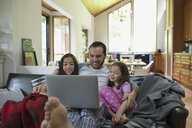 Father and daughters watching video on laptop on living room sofa - HEROF18607
