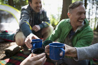 Friends toasting coffee mugs at campsite - HEROF18622