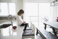 Girl using digital tablet on kitchen island - HEROF18664