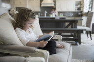 Girl reading book on living room sofa - HEROF18667